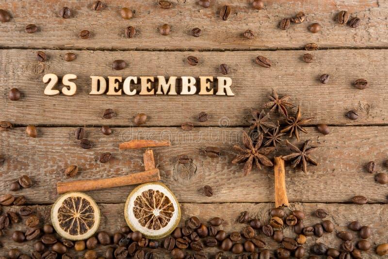 A inscrição das letras e dos números de madeira 'o 25 de dezembro ', uma bicicleta e uma árvore das especiarias no fundo de madei imagem de stock