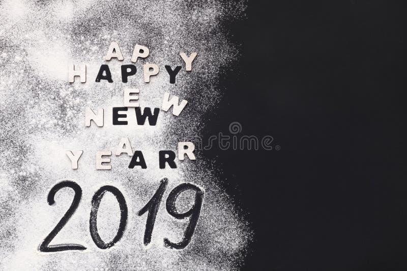 Inscrição 2019 do ano novo da farinha na tabela escura fotografia de stock royalty free