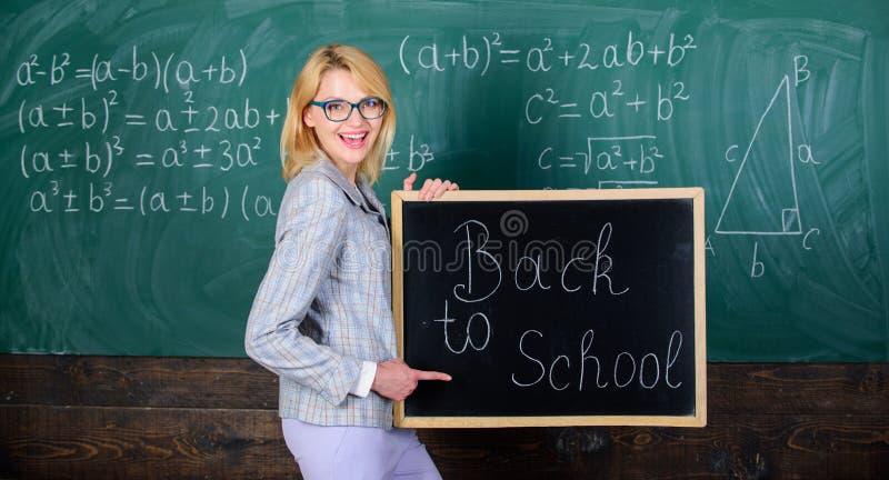 Inscrição do quadro-negro da posse da mulher do professor de volta à escola É tempo da escola outra vez Alunos bem-vindos felizes imagem de stock royalty free