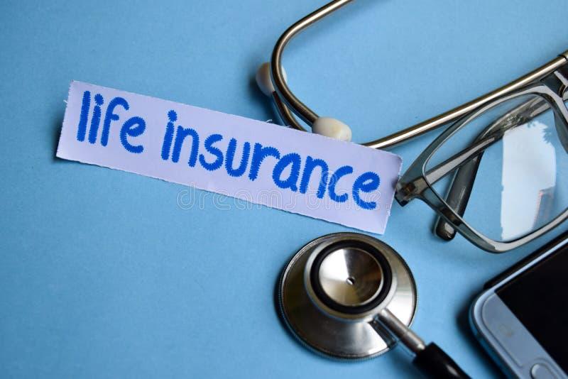 Inscrição do seguro de vida com a vista do estetoscópio, dos monóculos e do smartphone no fundo azul foto de stock royalty free