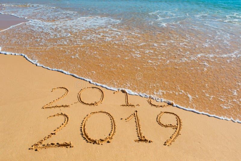 2018 2019 inscrição escritas na areia amarela molhada da praia que é imagens de stock