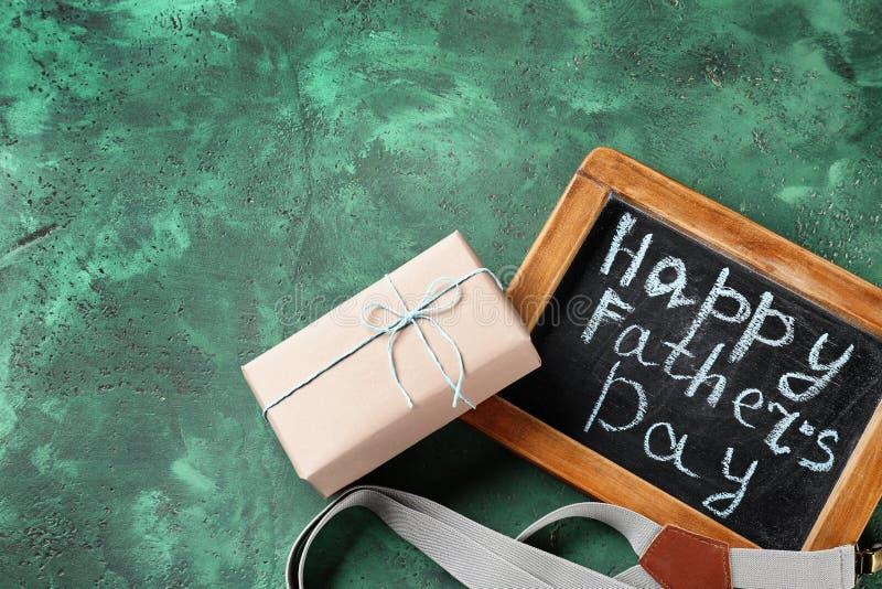 Inscrição feliz do dia de pai no quadro com suspensórios e caixa de presente em fundo textured da cor fotos de stock royalty free
