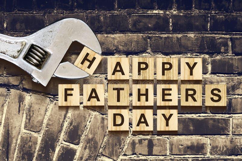 Inscrição feliz do dia de pais em cubos de madeira com ferramentas de funcionamento em uma parede de tijolo velha do vintage Conc imagens de stock