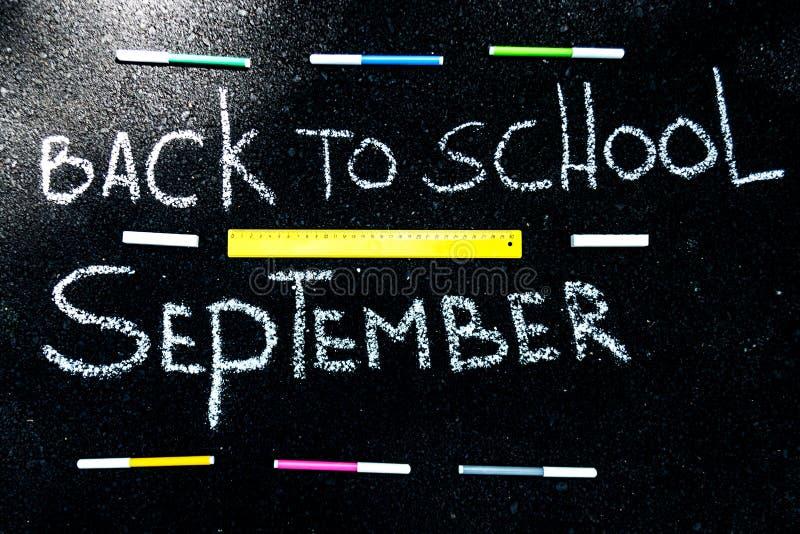 A inscrição no asfalto com giz branco de volta à escola, aos marcadores coloridos e à linha amarela fotos de stock royalty free