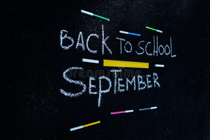 A inscrição no asfalto com giz branco de volta à escola, aos marcadores coloridos e à linha amarela fotos de stock
