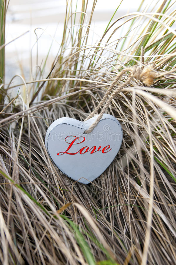 Inscribed blue wooden heart on beach dunes. Single blue wooden love heart in dunes on an Irish beach stock images