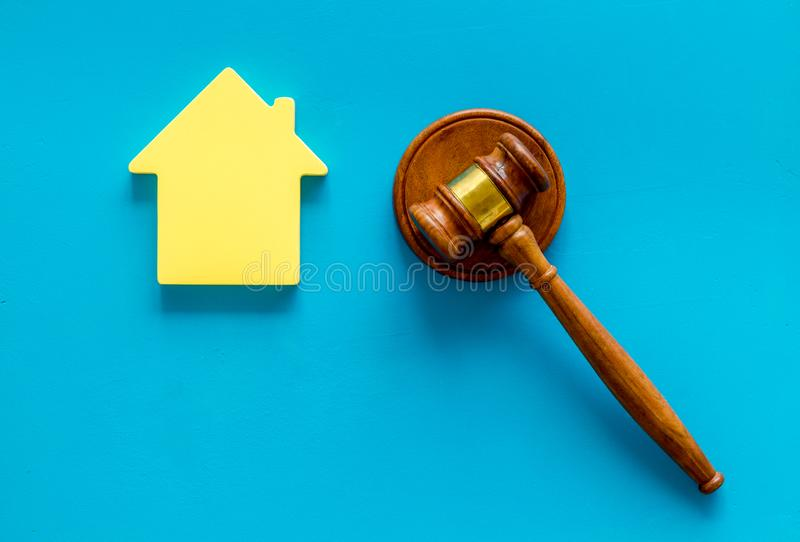 Inscribed gavel, house figure for inheritance concept on blue background top view.  royalty free stock photography