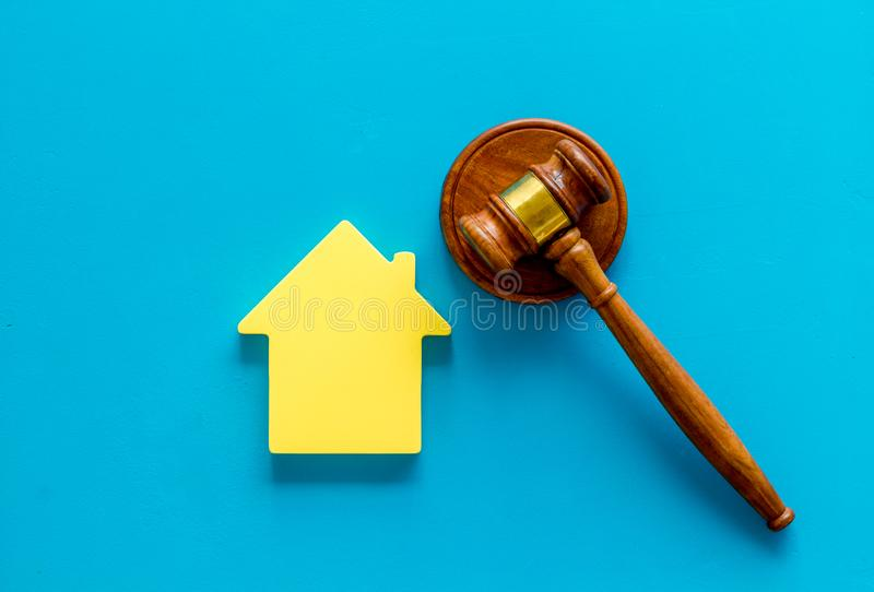 Inscribed gavel, house figure for inheritance concept on blue background top view.  stock image