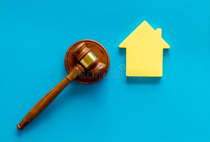 Inscribed gavel, house figure for inheritance concept on blue background top view.  royalty free stock photos