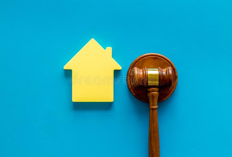 Inscribed gavel, house figure for inheritance concept on blue background top view.  stock photo