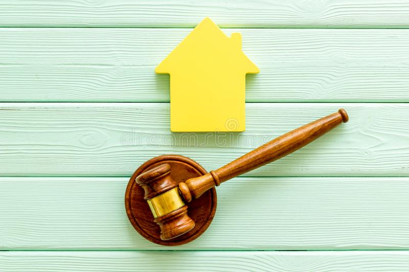 Inscribed gavel, house figure for inheritance concept on mint green wooden background top view.  royalty free stock photo