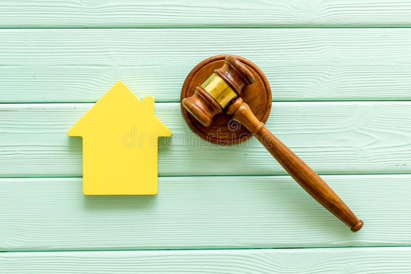 Inscribed gavel, house figure for inheritance concept on mint green wooden background top view.  royalty free stock photos
