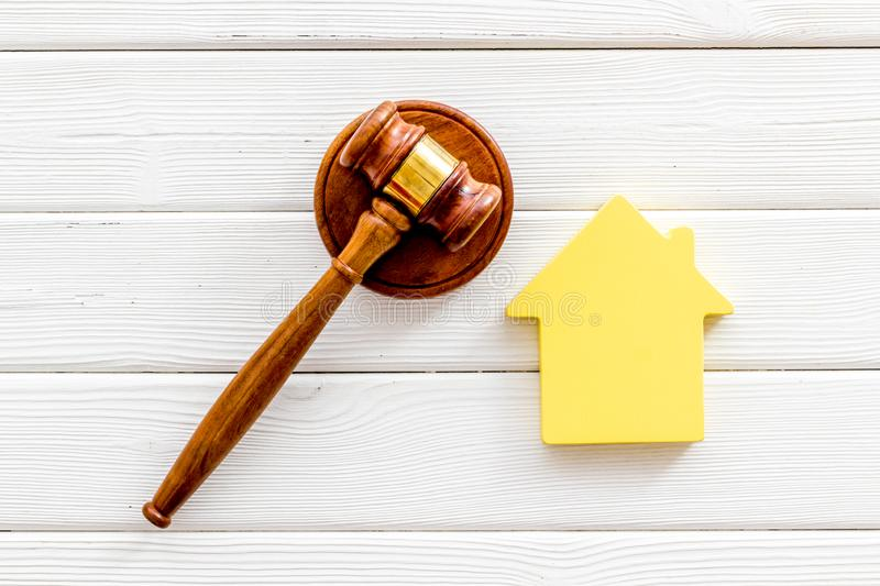 Inscribed gavel, house figure for inheritance concept on white wooden background top view.  royalty free stock image