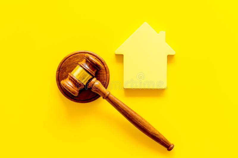 Inscribed gavel, house figure for inheritance concept on yellow background top view.  stock photos