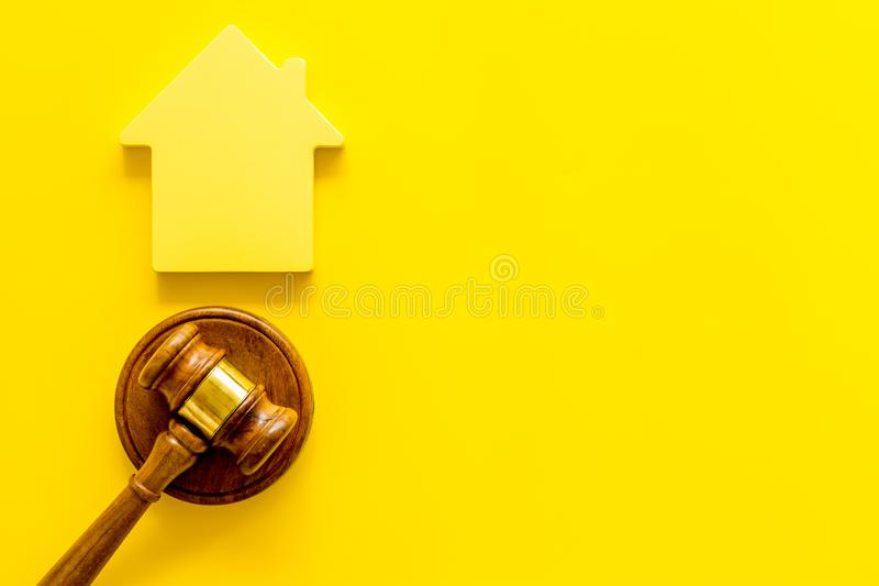 Inscribed gavel, house figure for inheritance concept on yellow background top view copyspace.  royalty free stock photography