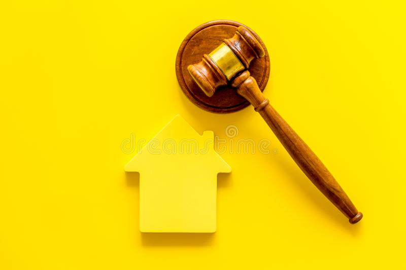 Inscribed gavel, house figure for inheritance concept on yellow background top view.  stock images