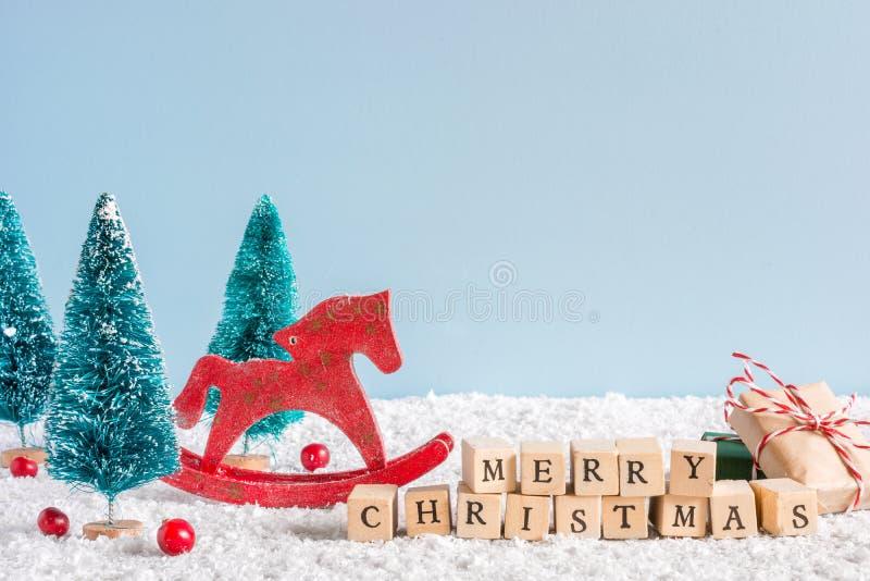Inscripción de la Feliz Navidad con el caballo retro del juguete, los abetos, las bayas rojas y la caja de regalo en la tabla de  fotos de archivo libres de regalías
