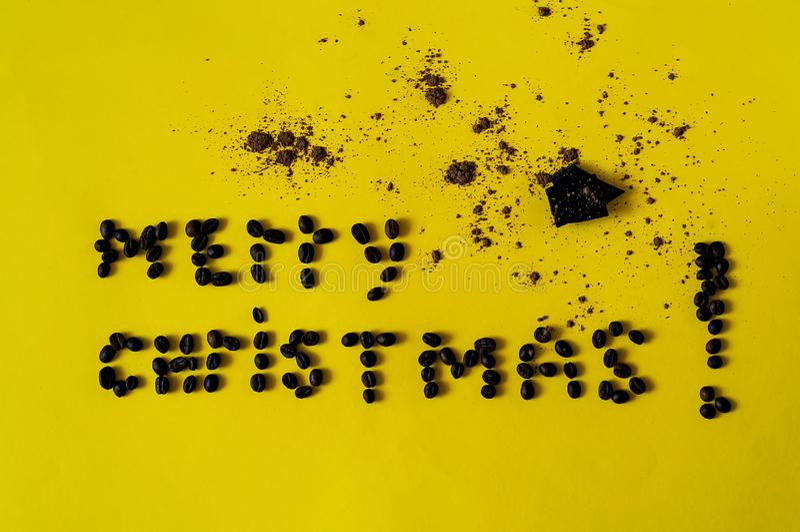 Inscripción de la Feliz Navidad, presentada de las habas del café Fondo del chocolate con en el texturecolor amarillo del year201 imagen de archivo