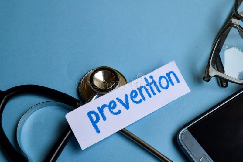 Inscripción de la prevención con la vista del estetoscopio, de lentes y del smartphone en el fondo azul imagen de archivo