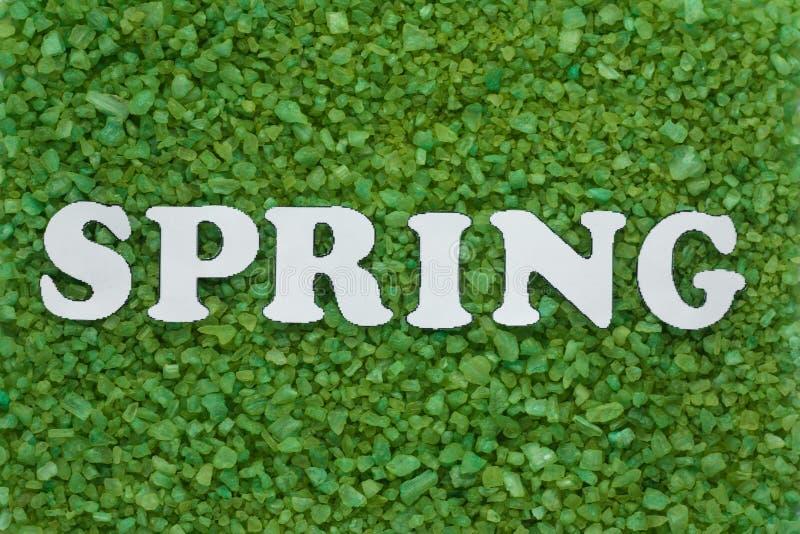 inscripción de la primavera en las letras blancas en un fondo verde de pequeños guijarros, abstracción estacional fotos de archivo libres de regalías