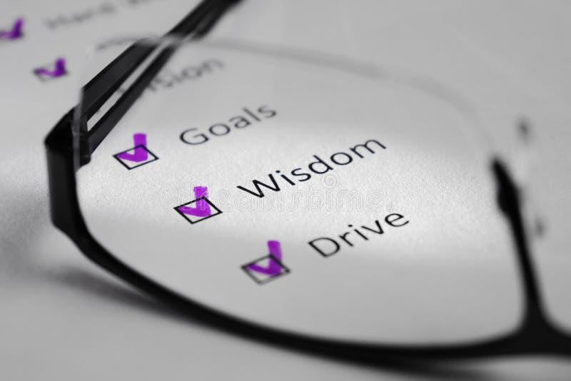 Inscripción de la SABIDURÍA en una hoja blanca Esto es una lista de control de motivación con los puntos para el éxito Enfrente d foto de archivo libre de regalías