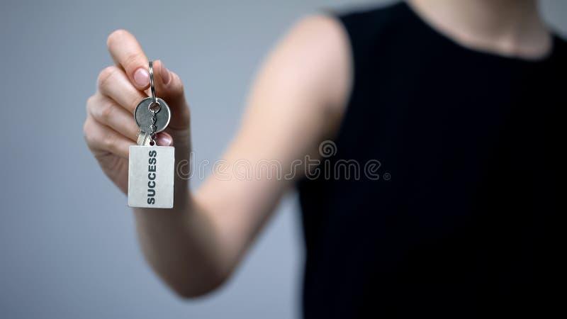 Inscripción del éxito en llavero en la mano de la mujer, extremidades para atraer el dinero, prosperidad fotografía de archivo