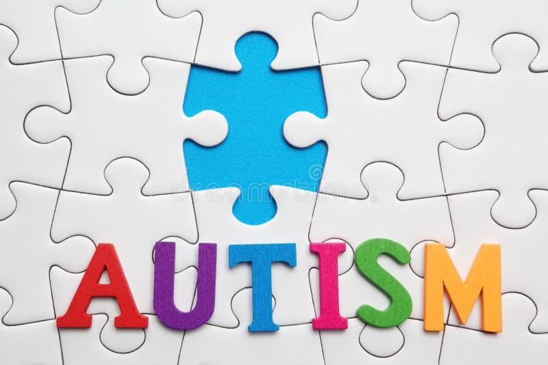 Inscripción del autismo en un fondo blanco del rompecabezas fotografía de archivo