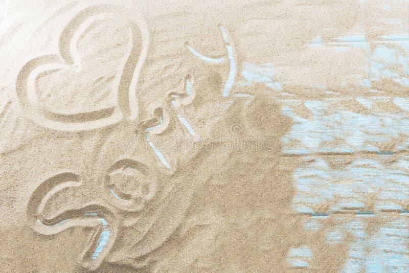 Inscripción en una playa arenosa en un fondo de madera ligero fotografía de archivo libre de regalías