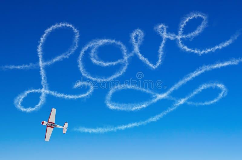 Inscripción figurada del amor de un aeroplano blanco del rastro del humo foto de archivo