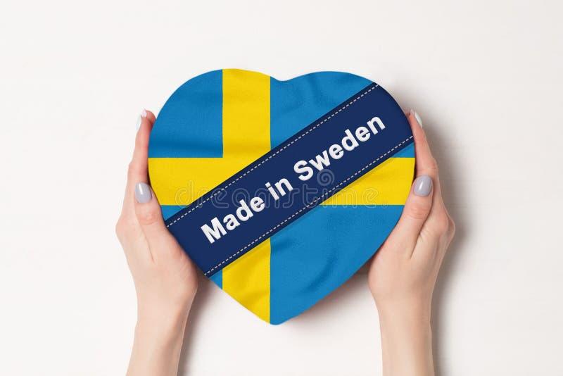 Inscripción Hecho en Suecia la bandera de Suecia. Manos femeninas sosteniendo una caja con forma de corazón. Fondo blanco fotografía de archivo libre de regalías
