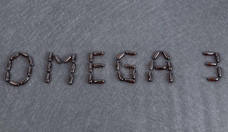 Inscripción Omega 3 en cápsulas negras del gel del fondo imagen de archivo