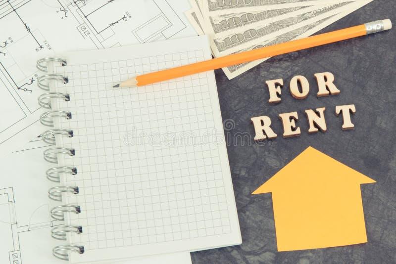 Inscripción para el alquiler, monedas dólar, libreta y diagramas eléctricos, casa de alquiler o concepto plano imagen de archivo
