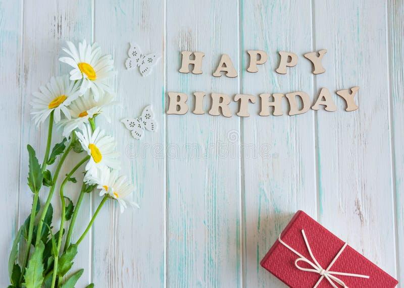 Inscripci?n del feliz cumplea?os Margaritas naturales en un fondo de madera con el feliz cumpleaños de la inscripción Dise?o de l foto de archivo libre de regalías