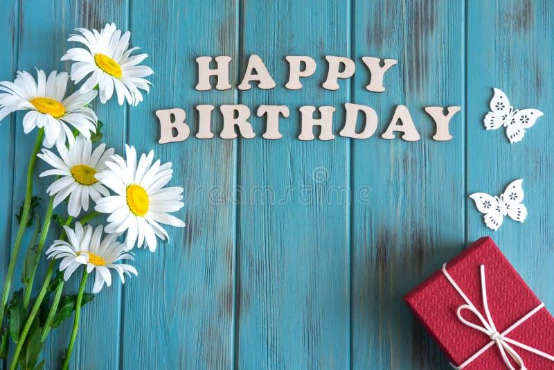 Inscripci?n del feliz cumplea?os Margaritas naturales en un fondo de madera con el feliz cumpleaños de la inscripción Dise?o de l imagen de archivo libre de regalías
