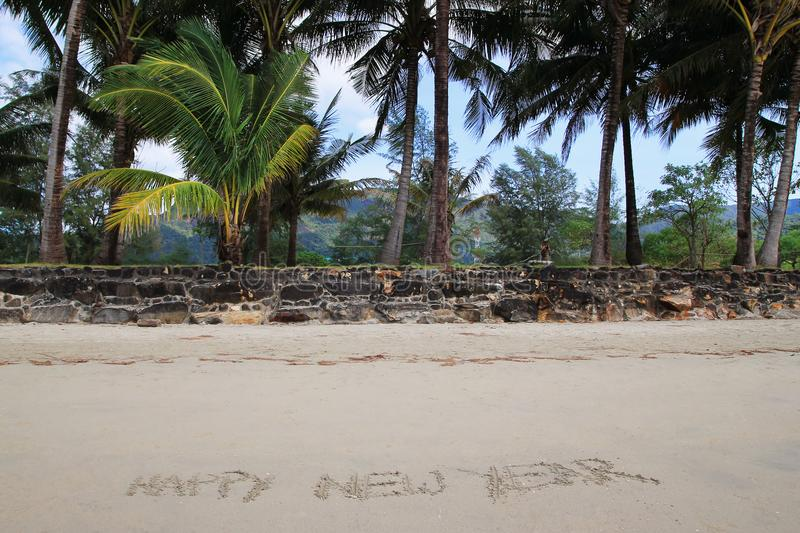 An inscription 'Happy New Year' on the sandy beach on the background of palm trees. stock photos