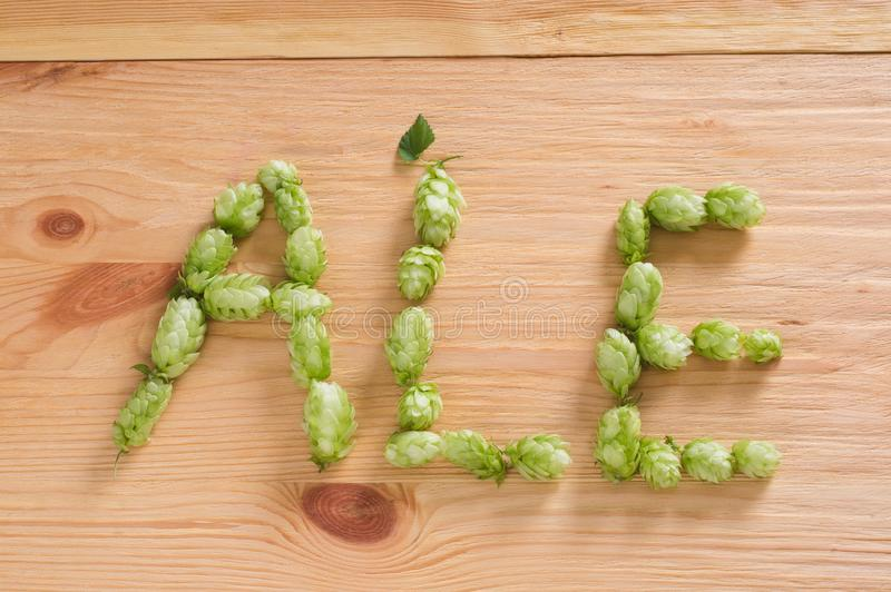 The inscription ale with hop cones on wooden background. Ingredient in beer industry. Craft beer brewing. For ale or lager royalty free stock image