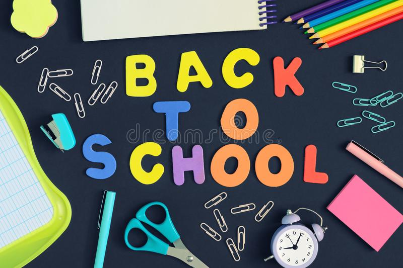 The inscription Back to School is made in colored letters. Multicolored picture on black background. stock image