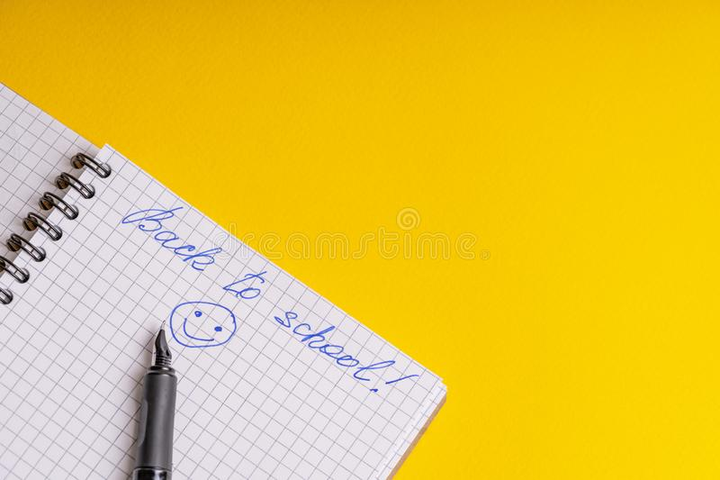 The inscription back to school and smile on a squared notebook and ink pen on a yellow background stock photography
