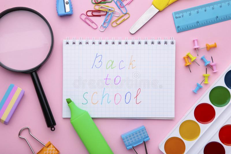 Inscription Back To School with school supplies on pink background royalty free stock images