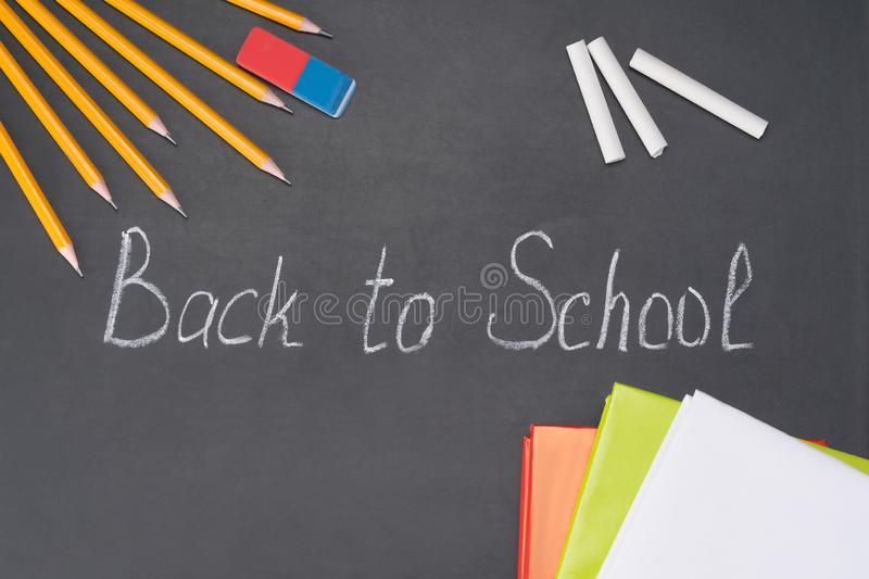 The inscription `back to school` is written in chalk on a blackboard among the stationery stock image