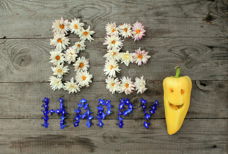 Inscription `Be happy` from flowers on wooden background with pepper in form of emoticon. Optimistic inscription `Be happy` from flowers on old unpainted wooden stock photos