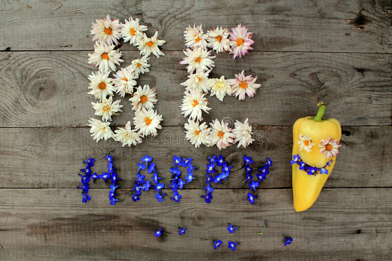 Inscription `Be happy` from flowers on wooden background with pepper in form of emoticon. Optimistic inscription `Be happy` from flowers on old unpainted wooden royalty free stock image