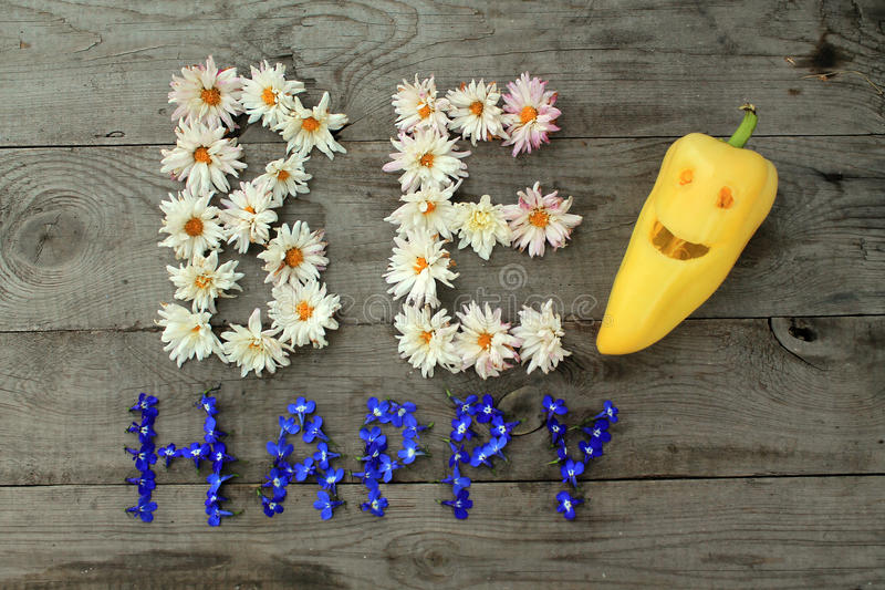 Inscription `Be happy` from flowers on wooden background with pepper in form of emoticon. Optimistic inscription `Be happy` from flowers on old unpainted wooden royalty free stock photos