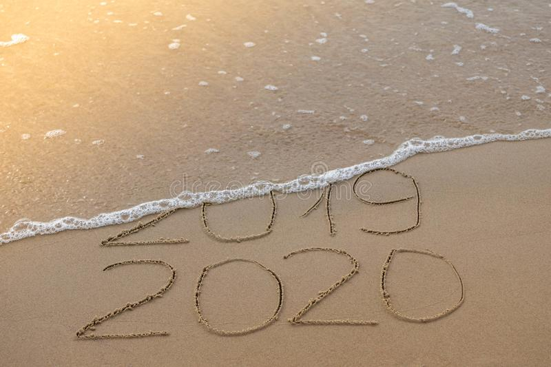 Inscription 2019 and 2020 on beach sand, wave covering 2019 digits. New Year 2020 coming concept. Handwritten inscription 2019 and 2020 on golden sand beach and royalty free stock images