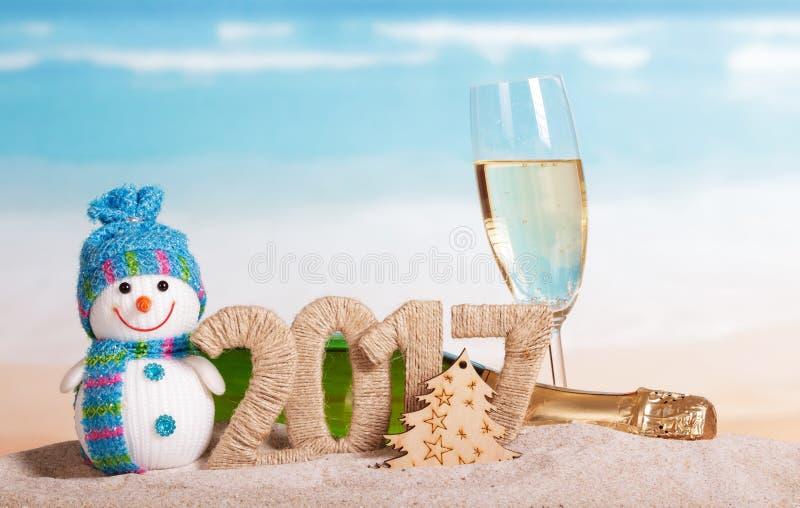 Inscription 2017, champagne, bonhomme de neige de Noël dans le sable photo libre de droits