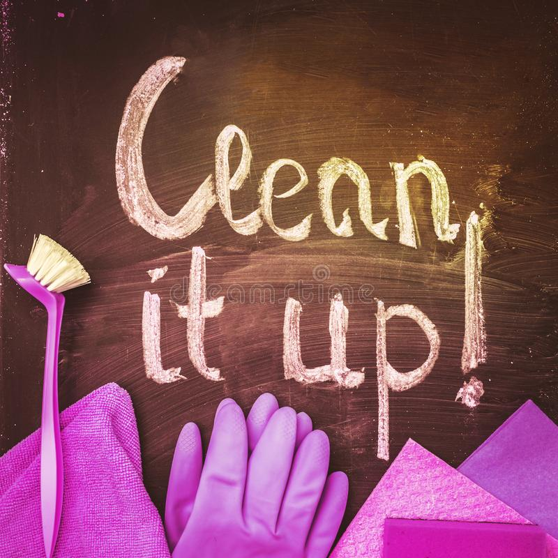 The words `clean it up!`on the chalkboard above the spring cleaning kit.. The inscription ` clean it up! `- on the chalkboard above the purple spring cleaning royalty free stock image