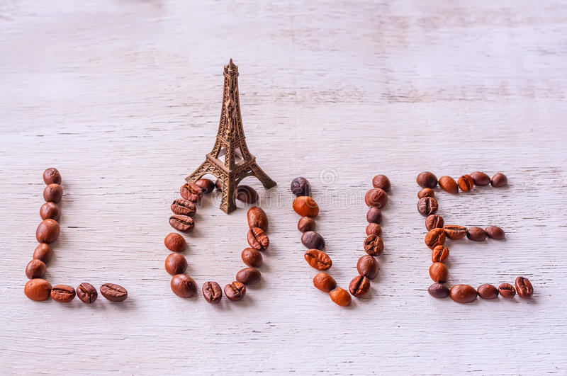 Inscription coffee beans word LOVE statue and Eiffel tower. On the old wooden light background royalty free stock photo