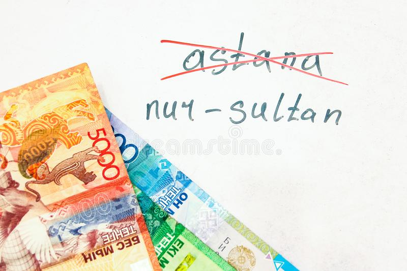 The inscription crossed out Astana, and the name of the new city of Nursultan, on a natural white background with the currency of stock photography