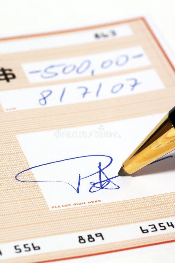 Inscription d'un chèque bancaire photographie stock libre de droits