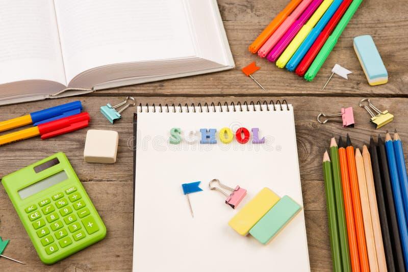 inscription de et x22 ; school& x22 ; , livre, calculatrice, bloc-notes et toute autre papeterie sur la table en bois brune photo stock